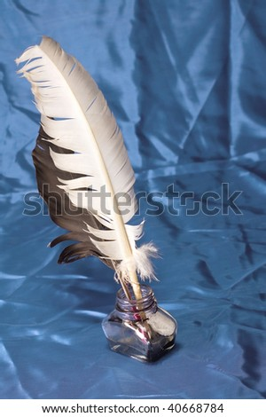 Feather quill and in well on texture of textile - stock photo
