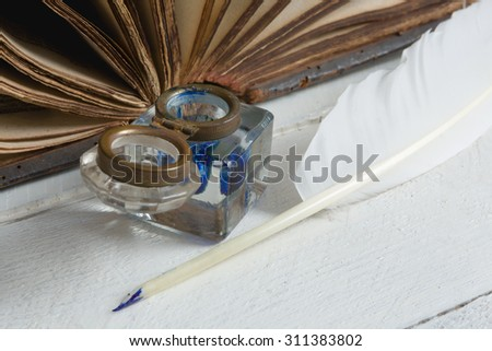 Feather quill, blue ink pot and medieval book on a rustic white painted table - stock photo