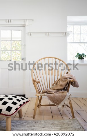 Feature wooden arm chair with throw and cushion ottoman in modern designer apartment - stock photo