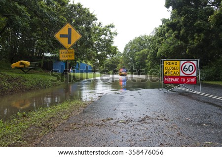 February 21, 2015: flooded road with road closed ahead roadsign. Yellow rural firebrigade four wheel drive vehicle crossing the floodwater. Palmwoods, Sunshine Coast, Queensland, Australia - stock photo