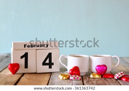 February 14th wooden vintage calendar with colorful heart shape chocolates next to couple cups on wooden table. selective focus. vintage filtered  - stock photo