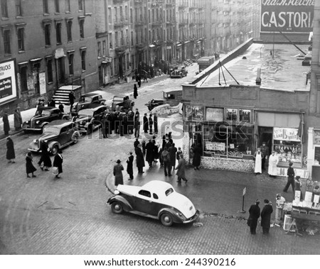 Federal Bureau of Narcotics agents blockade streets with their cars in a drug bust in the San Juan Hill neighborhood of New York City 1939. - stock photo