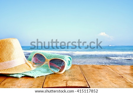 fedora hat and sunglasses over wooden table and sea landscape background. relaxation or vacation concept  - stock photo