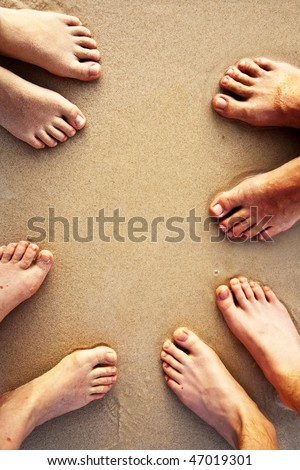 feed of the happy family, father, mother  and two suns at the sandy beach - stock photo