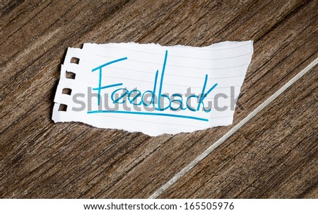 Feedback written on the paper on a wood background - stock photo