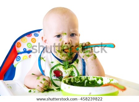 Feeding. Adorable baby child eating with a spoon in high chair. Baby's first solid food. Isolate on White - stock photo