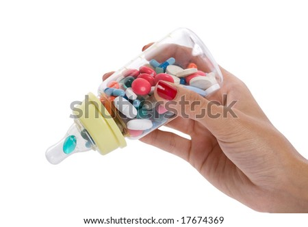feeding bottle filled with pills held by hand - stock photo