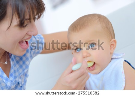 Feeding her baby boy - stock photo