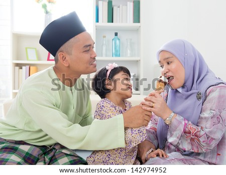 Feeding ice cream. Muslim girl feeding mother an ice cream. Beautiful Southeast Asian family living lifestyle at home. - stock photo