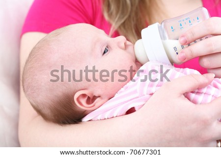 Feeding of the chest baby by a dairy mix from a children's small bottle