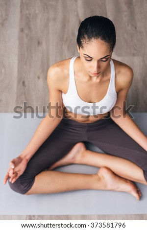 Feel all the energy inside you. Top view of beautiful young African woman in sportswear practicing yoga while sitting in lotus position on the floor
