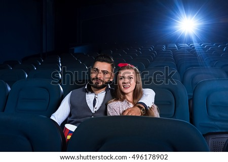 Feel-good movie. Handsome bearded man embracing his beautiful cheerful girlfriend while watching a movie at the local cinema together