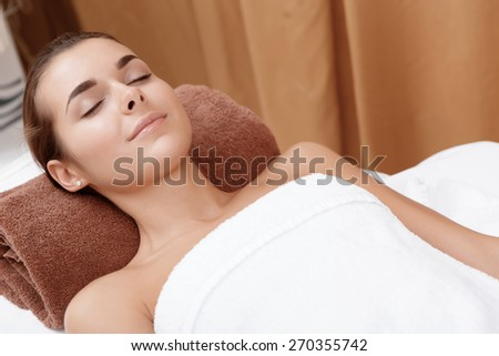 Feel gorgeous. Young beautiful woman relaxing with her eyes closed at cosmetologist room - stock photo