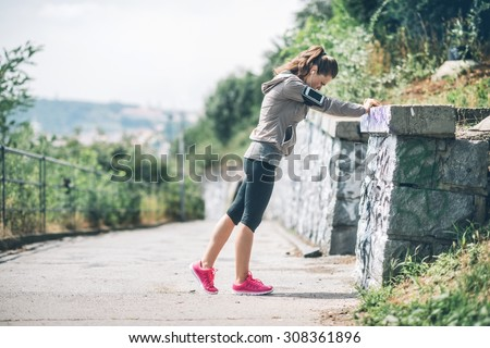 Feel that burn, and stretch those muscles... A woman wearing workout gear is using a rock wall to stretch out her legs before starting her run. - stock photo