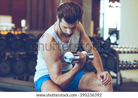 Feel the burn in bicep. Confident young handsome man in sportswear exercising with dumbbell at gym - stock photo