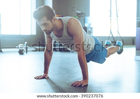 Feel your strength and balance. Full-length of young man in sportswear exercising at gym - stock photo