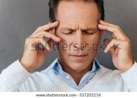 Feeling awful headache. Frustrated mature man touching his head with fingers and keeping eyes closed while standing against grey background