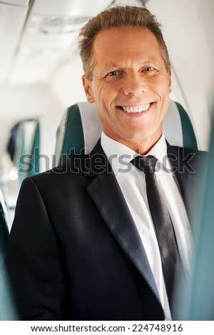 Feeling calm and safe. Confident mature businessman sitting at his seat in airplane and smiling - stock photo