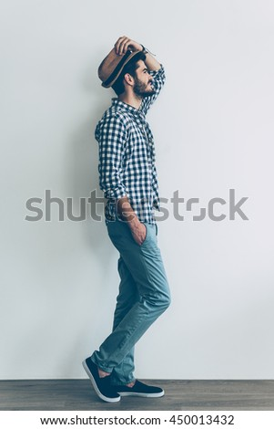 Feeling casual. Full length side view of handsome young cheerful man holding one hand in pocket and adjusting his hat - stock photo