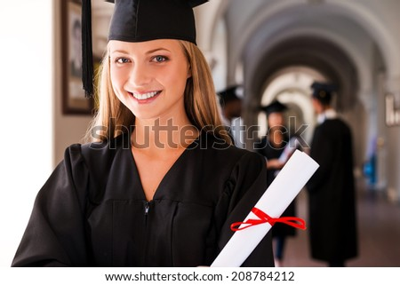 Feeling confident in her future. Happy young woman in graduation gowns holding diploma and smiling while her friends standing in the background  - stock photo