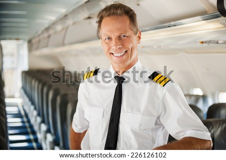 Feeling confident in his plane. Confident male pilot in uniform leaning at the passenger seat and smiling while standing inside of the airplane - stock photo