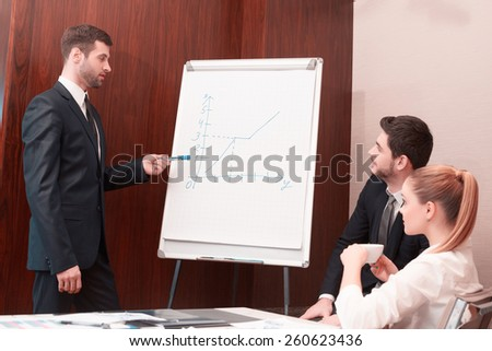 Feeling confident in his speech. Group of business people in formal wear sitting together at the table while handsome man standing near whiteboard and pointing it with smile - stock photo
