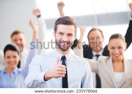 Feeling confident in his team. Happy businessman showing his thumb up and smiling while his colleagues standing in the background  - stock photo