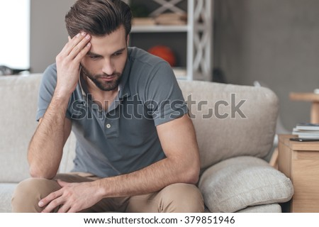 Feeling depressed. Desperate young man keeping his hand on forehead while sitting on the couch at home - stock photo