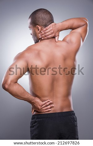 Feeling discomfort. Rear view of young muscular African man touching his hip and neck while standing against grey background - stock photo