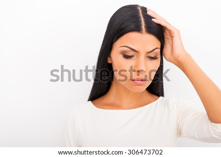 Feeling exhausted. Depressed young woman touching her head and looking down while standing against white background