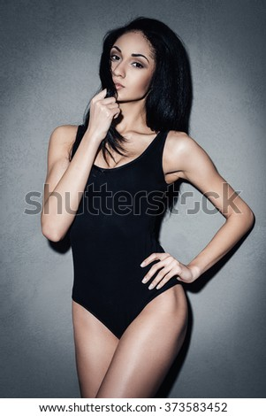 Feeling flirty. Beautiful young African woman in black swimsuit holding hand on hip and looking at camera while standing against grey background - stock photo