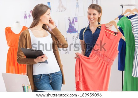 Feeling happy about new collection. Two attractive women looking at each other while one of them holding dress and smiling