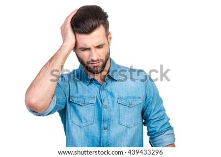 Feeling headache. Frustrated young handsome man in jeans shirt touching his head with hand and keeping eyes closed while standing against white background  - stock photo