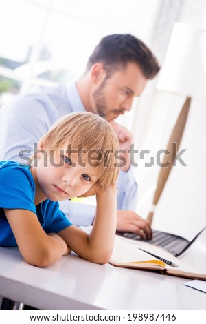 Feeling lonely. Depressed little boy holding hand in hair and looking at camera while his busy father working in the background  - stock photo