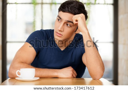Feeling lonely. Frustrated young man sitting at the restaurant and holding head in hand