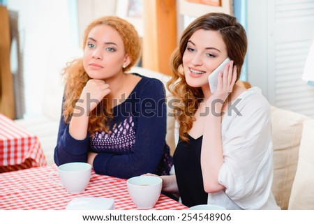 Feeling lonely near her. Sad beautiful woman sitting in cafe while her girl friend talking over their cell phone - stock photo