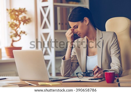 Feeling overworked. Frustrated young beautiful businesswoman looking exhausted while sitting at her working place and carrying her glasses in hand - stock photo