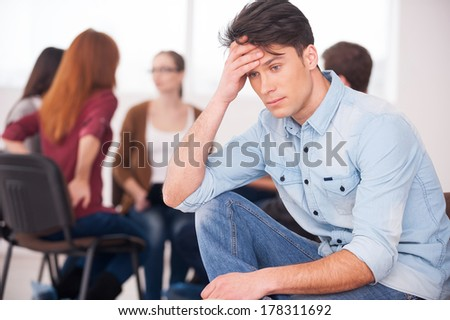 Feeling pain and depression. Depressed young man sitting at the chair and holding head in hand while other people communicating on background  - stock photo