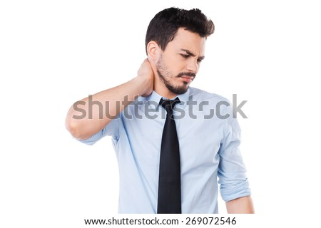 Feeling pain in neck. Frustrated young man in shirt and tie touching his neck and expressing negativity while standing against white background - stock photo