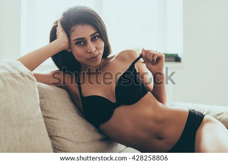 Feeling playful. Beautiful young mixed race woman in black lingerie looking at camera and taking off her bra while sitting on couch at home - stock photo