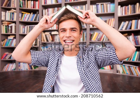 Feeling playful. Cheerful young man carrying book on head and smiling while sitting against bookshelf - stock photo