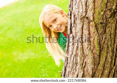 Feeling playful. Cute little girl looking out of the tree and smiling while standing outdoors - stock photo