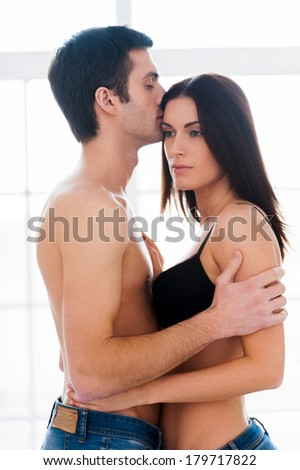 Feeling protected in his hands. Side view of beautiful young loving couple in underwear hugging - stock photo