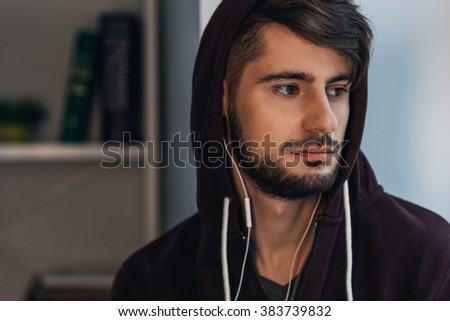 Feeling sad. Portrait of pensive young man in hooded shirt looking away while standing at home - stock photo