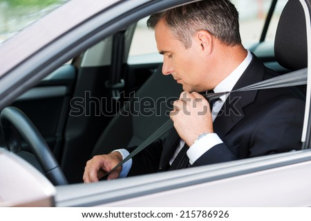 Feeling safe in new car. Confident mature businessman fastening seat belt while sitting in his car  - stock photo