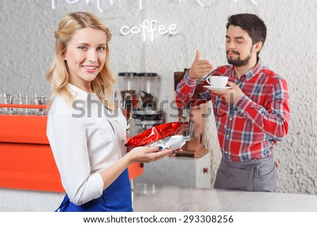 Feeling satisfaction. Portrait of pretty young blond-haired barista standing with coffee packages on background of satisfied customer. - stock photo