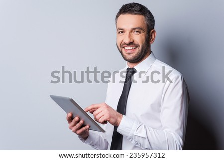 Feeling satisfied with his new gadget. Confident mature man in shirt and tie working on digital tablet and smiling while standing against grey background - stock photo