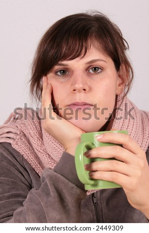 Feeling Sick this young beautiful woman drinks a cup of tea. her facial expression shows that she is feeling sick.