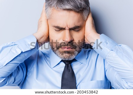 Feeling stressed and overworked. Frustrated mature man in shirt and tie covering ears with hands and keeping eyes closed while standing against grey background
