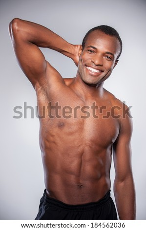 Feeling strong and confident. Young African man holding hand behind head looking at camera and keeping arms crossed while standing isolated on grey background - stock photo